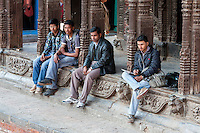 Nepal, Patan.  Young Nepalese Men Hanging Out at the Vishwanath Mandir.  The Vishwanath temple survived the earthquake of April 2015.
