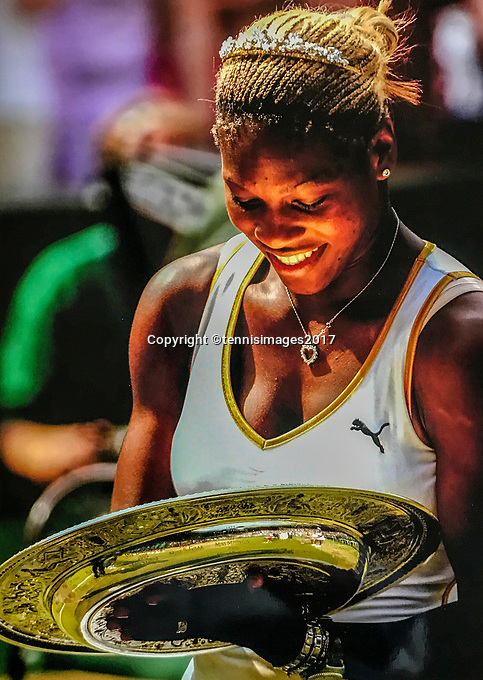 Serena Williams with the Wimbledon Trophy witch is reflecting sunlight in her face.