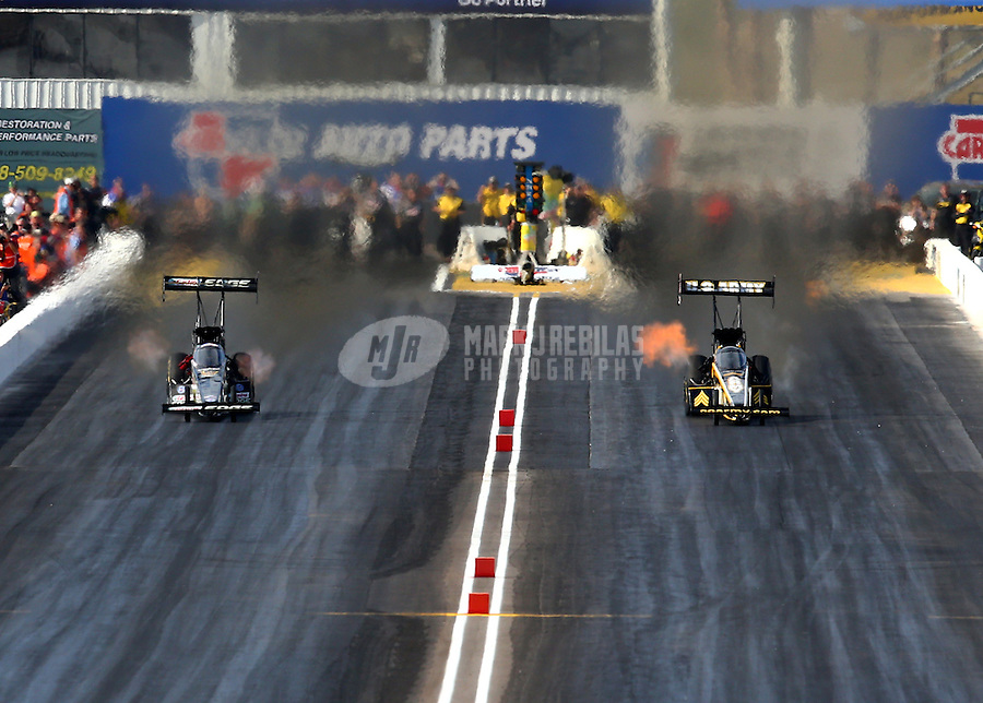 Feb 21, 2014; Chandler, AZ, USA; NHRA top fuel dragster driver Brittany Force (left) races alongside Tony Schumacher during qualifying for the Carquest Auto Parts Nationals at Wild Horse Pass Motorsports Park. Mandatory Credit: Mark J. Rebilas-USA TODAY Sports