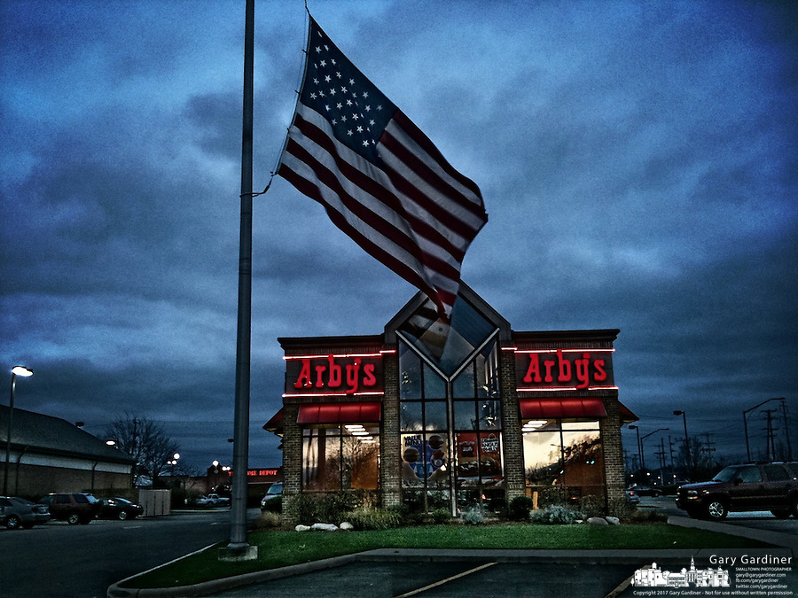 An American flag flies at half-staff over an Arby's restaurant in Westerville Ohio in commemoration of Pearl Harbor Day, Dec. 7, 2011.