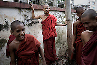 A group of novice monks make repairs to their monastery in central Rangoon after heavy rains.