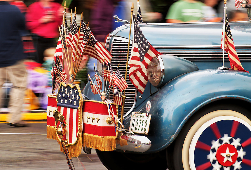 Classic car adorned with US flags and regalia driving in parade to celebrate Kla Ha Ya Days, Snohomish, Snohomish County, Washington, US