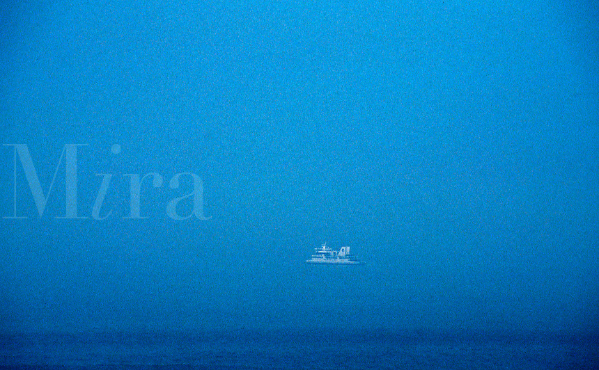 A lone boat makes its way through the fog in the Atlantic Ocean off Cape May, New Jersey