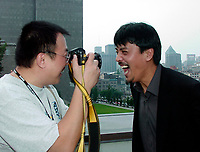 August 30, 2000, Montreal, Quebec, Canada<br /> <br /> -Jian Qi, Director  `` Female coaxh leading male sportsmen `` (R) snap a photo of <br /> Sun Zhou ; Director ``Broken Silence `` featuring Gong Li, August30, 2000 at the Reception given by the City of Montreal during the World Film Festival.<br /> <br /> Photo  (c)2000,  Pierre Roussel - Images Distribution