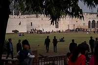 People gather in grassy areas near buildings inside the Red Fort in Delhi, India, on Tue., Dec. 11, 2018.