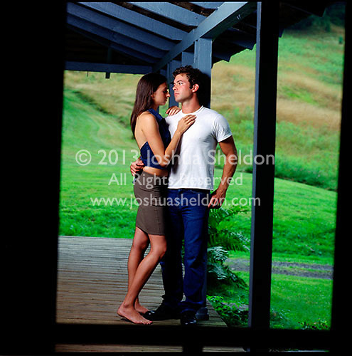 Couple standing on porch embracing seen through screen door<br />