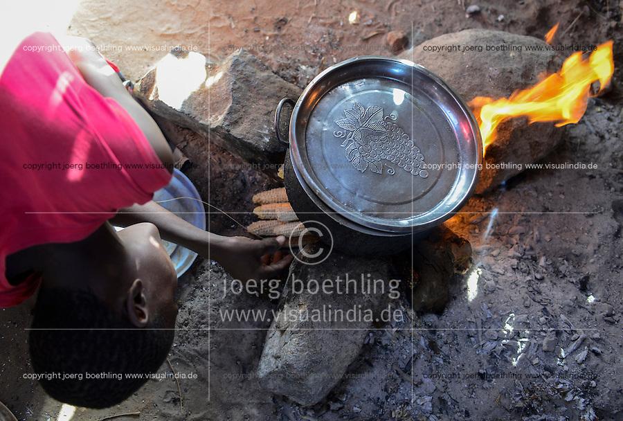 KENYA Turkana, Lodwar,village Kaitese, Turkana tribe, woman cook in kitchen, using remains of corncob as fuel / KENIA, Turkan Dord Kaitese, Herdstelle, Brennstoff Reste von Maiskolben