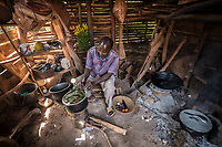 Uganda, Wamala. Teddy Kalema and her husband Charles, cooking on the Biolite cook stove in their home. This system also charges a light and their mobile phone.