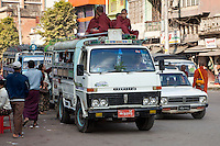 Myanmar, Burma, Mandalay.  Novice Monks Riding on top of a Van in downtown Mandalay Traffic.