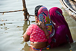 Indian women in traditional dress bathing and making offerings at the Ganges River in Allahabad for Kumbh Mela Festival.