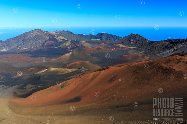 A view into the magnificent red and brown crater of Haleakala with blue sky and ocean in the distance, Maui.