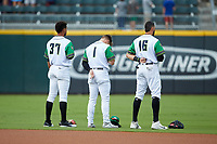 (L-R) Caballeros de Charlotte outfielders Jacob Scavuzzo (37), Charlie Tilson (1), and Paulo Orlando (16) stand for the National Anthem prior to the game against the Buffalo Bisons at BB&T BallPark on July 23, 2019 in Charlotte, North Carolina. The Bisons defeated the Caballeros 8-1. (Brian Westerholt/Four Seam Images)