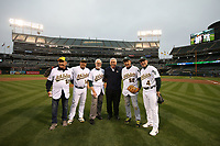 OAKLAND, CA - AUGUST 14:  Photographer Doug McWilliams, Oakland Athletics team photographer Michael Zagaris, and photographer Ron Riesterer pose with A's coaches Chip Hale #4, Mike Aldrete #14 along with A's broadcaster Ray Fosse after throwing out a ceremonial first pitch before the game between the Kansas City Royals and Oakland Athletics at the Oakland Coliseum on Monday, August 14, 2017 in Oakland, California. (Photo by Brad Mangin)