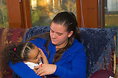MR / Schenectady, NY. Mother (21) cuddles with her toddler daughter (2, African American & Caucasian). MR: Dal5, Dal6. ID: AL-HD. © Ellen B. Senisi