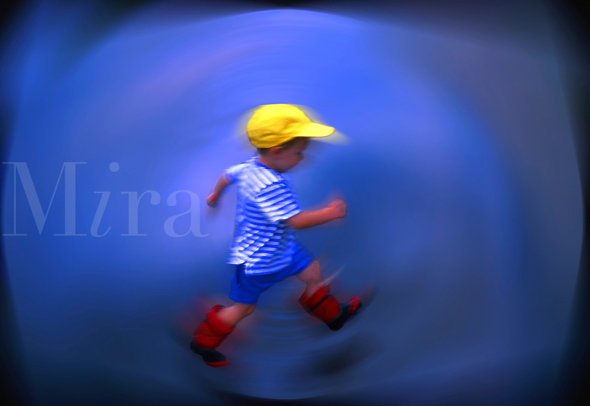 Boy Jumping Over Rain Puddle. Digitally enhanced photograph. Child Running.