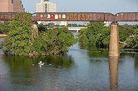 A kayaker passes by the fun and inspiring graffiti paintings on the Austin Railroad Graffiti Bridge over Lady Bird Town Lake, Austin, Texas.