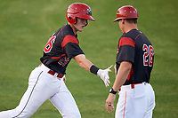 Batavia Muckdogs catcher Jared Barnes (26) shakes hands with manager Mike Jacobs (28) after hitting a home run during a game against the Auburn Doubledays on August 26, 2017 at Dwyer Stadium in Batavia, New York.  Batavia defeated Auburn 5-4.  (Mike Janes/Four Seam Images)
