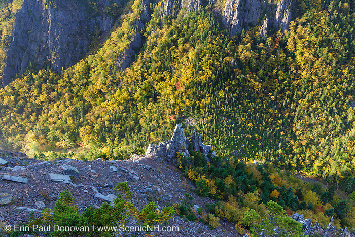 Dixville Notch State Park in New Hampshire from a scenic viewpoint along the Sanguinary Ridge Trail during the autumn months. A hiker can be seen on the trail in the lower right of the scene.