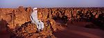 Au sud ouest du désert Libyen, le tassili du Maghidet est un fantastique dédale rocheux s'étirant sur un croissant de sable rose de plus de 45 km de long. Au lever du soleil, on contemple en silence l'ombre des milliers de tourelles et aiguilles rocheuses qui avance en bataillons sérrés suivant la progression du soleil. Maghidet, Désert de Libye. Libye.