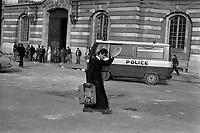 . 27 février 1985. Au 1er plan étudiant en soutane , tient dans une main un carton contenant les restes des grenades lacrymogènes ; en arrière-plan fourgon de police stationné devant le Capitole, groupe de personnes devant l'entrée ; débris sur le sol. Cliché pris lors du Carnaval universitaire pendant lequel des incidents ont éclaté entre des étudiants et les forces de l'ordre.
