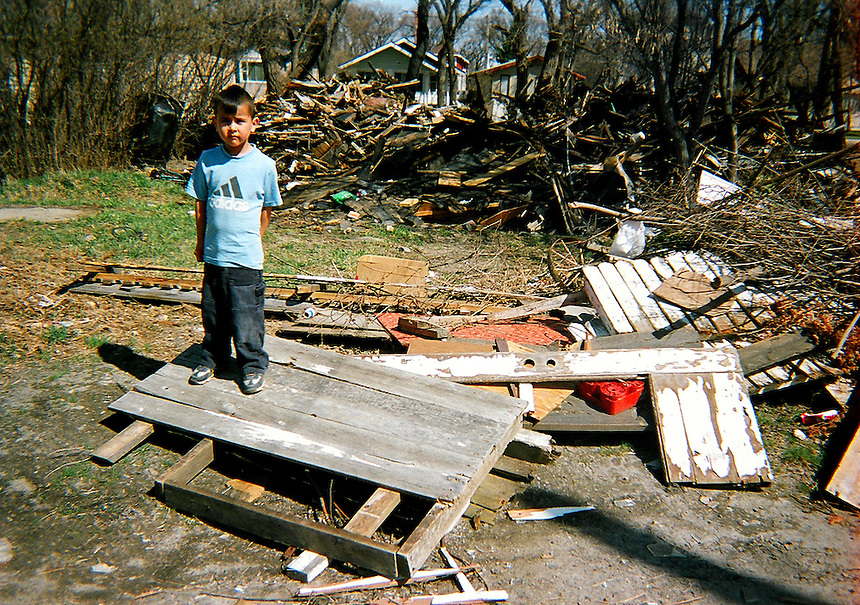 A boy poses for a picture while playing amongst the debris of a demolished North Central home. MARK TAYLOR GALLERY