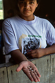 Amazon, Brazil. Serious woman showing two wedding rings, made of local gold from a garimpo placer mine.