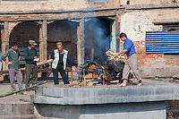 Nepal, Pashupatinath.  Cremation Stages.  Adding Kindling Wood to a Fire already Begun.