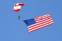 The stars and stripes makes its way down to earth beneath the canopy of a parachutists during the 2010 Madera Gathering of Warbirds in Madera, California
