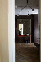 In the hallway the chevron flooring is made of French reclaimed oak whilst the simple furniture has a retro feel.