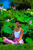 Woman meditating on lush grass surrounded by pink lotus flowers.