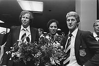 Olympic Team back from Montreal, from left to right Evert Kroon (water polo team keeper), Enith Brigitha (swimmer) and Herman Ponsteen (track cyclist) in the flowers<br /> Date August 3, 1976<br /> <br /> Photographer Peters, Hans / Anefo