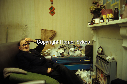 Kingston upon Hull, Humberside. 1980<br /> In his two up two down terraced home, warming himself in front of his gas fire; Billy Whitehead a 87 year old retired seaman chats over a four o'clock cup of tea about how life has changed in recent years.