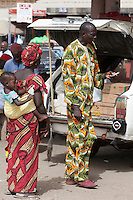 Senegal, Saint Louis.  Colorful African Clothing at Bus and Taxi Station.  The man is using a chewing stick to clean his teeth.