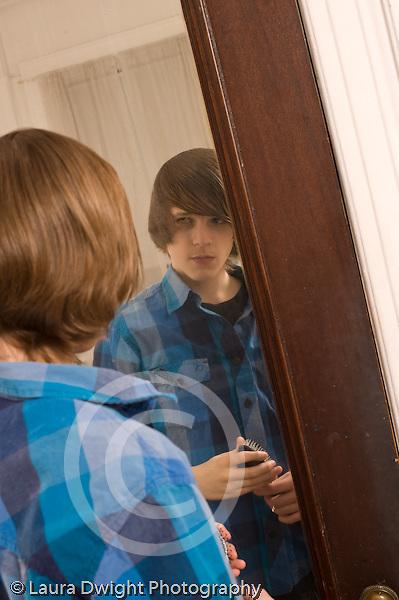 Teenage boy looking at self in mirror Caucasian vertical age 14