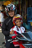 Yogyakarta, Java, Indonesia.  Two Young Men with Helmets on a Motorbike, Bird Market.
