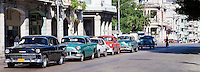 Cuba, Havana.  Antique American Cars as Taxis, Waiting at a Red Light.