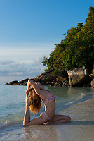 Yoga on the beach in Thailand - girl in pigeon pose on Sunrise beach, Ko Lipe island