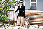 A sophistocated woman standing with her dog next to her home and rose garden