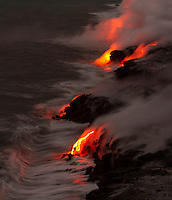 Active lava meets crashing waves on the coastline along Kalapana and Hawai'i Volcanoes National Park, Big Island, Hawaii.