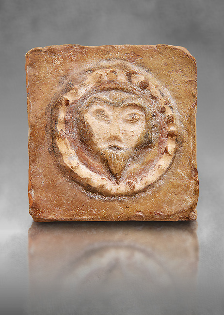 6th-7th Century Eastern Roman Byzantine  Christian Terracotta tiles depicting Christ - Produced in Byzacena -  present day Tunisia. <br /> <br /> These early Christian terracotta tiles were mass produced thanks to moulds. Their quadrangular, square or rectangular shape as well as the standardised sizes in use in the different regions were determined by their architectonic function and were designed to facilitate their assembly according to various combinations to decorate large flat surfaces of walls or ceilings. <br /> <br /> Byzacena stood out for its use of biblical and hagiographic themes and a richer variety of animals, birds and roses. Some deer and lions were obviously inspired from Zeugitana prototypes attesting to the pre-existence of this province's production with respect to that of Byzacena. The rules governing this art are similar to those that applied to late Roman and Christian art with, in the case of Byzacena, an obvious popular connotation. Its distinguishing features are flatness, a predilection for symmetrical compositions, frontal and lateral representations, the absence of tridimensional attitudes and the naivety of some details (large eyes, pointed chins). Mass production enabled this type of decoration to be widely used at little cost and it played a role as ideograms and for teaching catechism through pictures. Painting, now often faded, enhanced motifs in relief or enriched them with additional details to break their repetitive monotony.<br /> <br /> The Bardo National Museum Tunis, Tunisia. Against a grey art background.