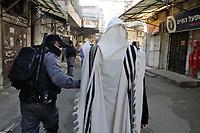 Un Haredi o temeroso de dios cubierto con el manto de rezo o talit, es detenido por la policía antidisturbios en el barrio ultra ortodoxo Mea Shearim mientras rezaba a tempranas horas de la mañana en una sinagoga, violando la prohibición impuesta por el Ministerio de Salud de rezar en sinagogas durante el confinamiento decretado como parte de la lucha contra el COVID 19. Las autoridades israelies declararon la ciudad  ultrareligiosa Bnei Brak y los barrios ultra ortodoxos de Jerusalén bajo sitio en un esfuerzo por controlar el contagio de la pandemia.<br /> Foto Quique Kierszenbaum