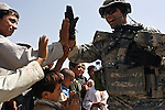 Staff Sgt. David Ditullio, 37, of Grand Island, N.Y., exchanges high-fives with a group of boys waiting to receive free medical assistance, food staples and winter clothes from U.S. troops and Afghan police in Kandahar, Afghanistan. Aug. 18, 2008. DREW BROWN/STARS AND STRIPES
