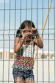 A Kayapo girl in western clothes but with traditional close-cropped strip of hair laughs through a wire mesh fence during the International Indigenous Games in Brazil. 26th October 2015
