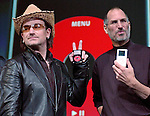 Bono, left, of the band U-2, and Apple Computers Inc. Chief Executive Steve Jobs, right, hold up Apple iPods at an unveiling of a new branded iPod in San Jose, Calif., Tuesday, Oct. 2, 2004.  Bono is holding up a new iPod with a red dial and black casing.  (AP Photo/Paul Sakuma)
