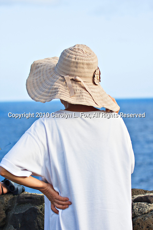 A woman, wearing a tan hat, stands by a stone wall looking out to sea.