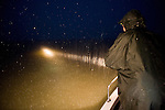 In pouring rain, Guido Westhoff spotlighting the water surface looking for sea snakes to catch at night.