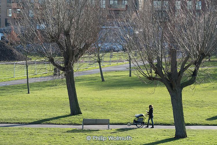 Woman with a pram. Burgess Park, Southwark.