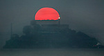 The sunrise briefly broke through the thick morning fog offering a short blast of warmth as seen over Alcatraz Island from Sausalito, California..