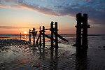 Great Britain, England, East Riding of Yorkshire, Spurn Head near Kingston upon Hull: decaying wooden posts of old pier at sunset | Grossbritannien, England, East Riding of Yorkshire, Spurn Head bei Kingston upon Hull: Ueberreste einer hoelzernen Pier, Sonnenuntergang am Strand