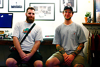 """Photographer Justin Boyd (left) and Pat Bruener (right), owner of Bankrupt Bodega, pose for a portrait during """"Proper Nouns', a photography show by Justin Boyd, at Bankrupt Bodega in the Bloomfield neighborhood on Friday September 3, 2021 in Pittsburgh, Pennsylvania. (Photo by Jared Wickerham/Pittsburgh City Paper)"""